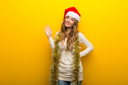 Girl celebrating the christmas holidays on yellow background saluting with hand with happy expression