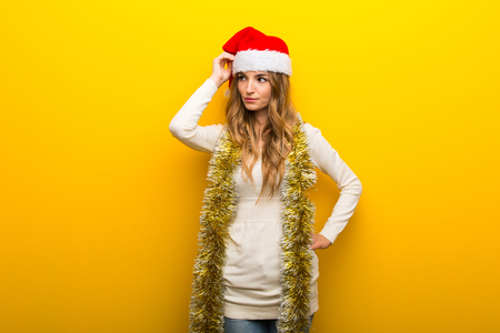 Girl celebrating the christmas holidays on yellow background having doubts while scratching head