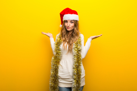 Girl celebrating the christmas holidays on yellow background having doubts while raising hands and shoulders
