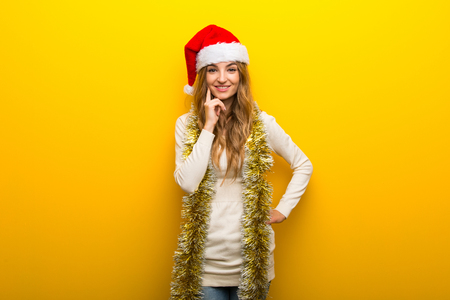 Girl celebrating the christmas holidays on yellow background smiling and looking to the front with confident face
