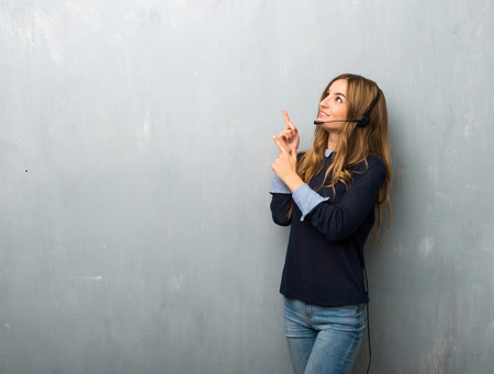 Telemarketer woman pointing with the index finger and looking up Stock fotó