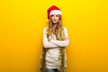 Girl celebrating the christmas holidays on yellow background with confuse face expression while bites lip