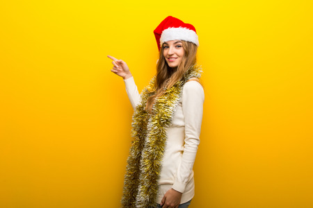 Girl celebrating the christmas holidays on yellow background pointing finger to the side in lateral position 版權商用圖片