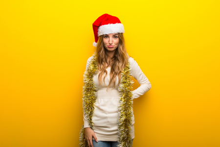 Girl celebrating the christmas holidays on yellow background with sad and depressed expression Stock Photo