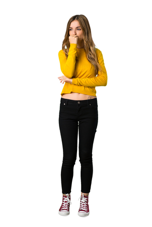 A full-length shot of a young girl with yellow sweater having doubts on isolated white background Archivio Fotografico