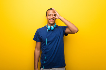 African american man with blue t-shirt on yellow background makes funny and crazy face emotion Reklamní fotografie