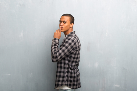 Young african american man with checkered shirt showing a sign of closing mouth and silence gesture