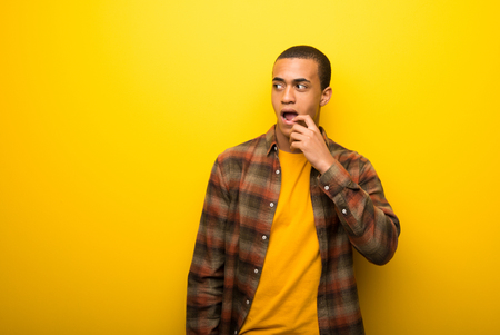 Young african american man on vibrant yellow background having doubts while looking up Stock Photo