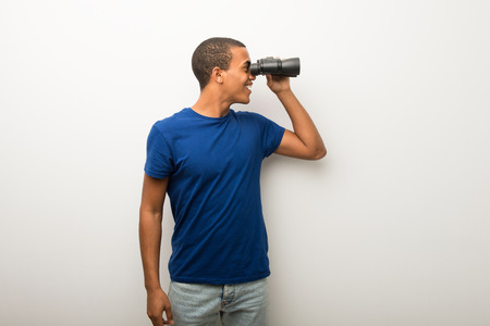 Young african american man on white wall and looking in the distance with binoculars Stok Fotoğraf