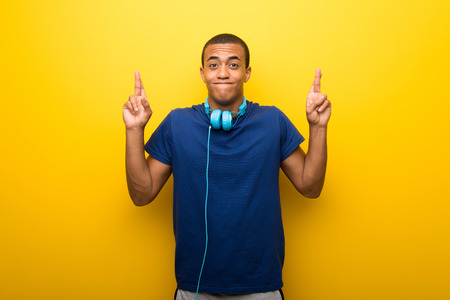 African american man with blue t-shirt on yellow background with fingers crossing and wishing the best