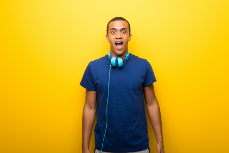 African american man with blue t-shirt on yellow background with surprise and shocked facial expression