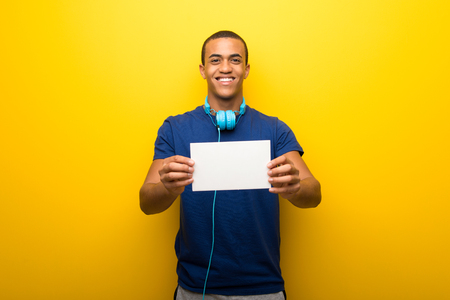 African american man with blue t-shirt on yellow background holding an empty white placard for insert a concept