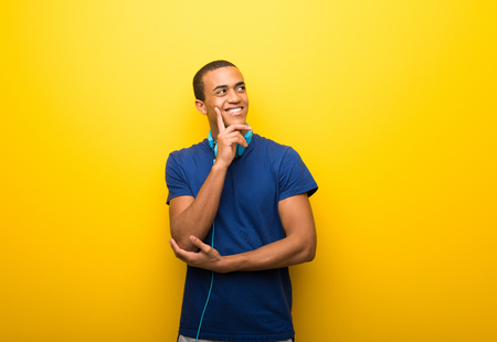 African american man with blue t-shirt on yellow background thinking an idea while looking up Stock Photo