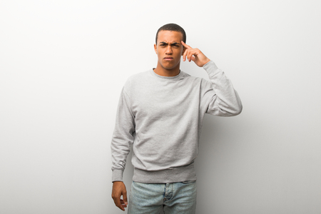 African american man on white wall background making the gesture of madness putting finger on the head