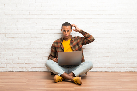 African american man sitting on the floor with his laptop having doubts while scratching head