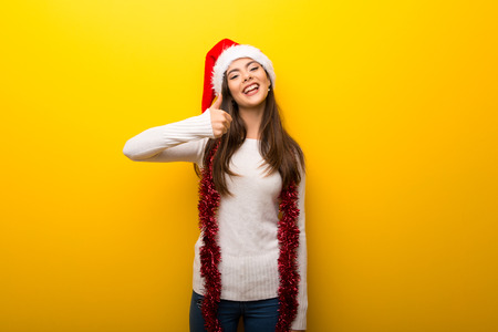 Teenager girl celebrating christmas holidays giving a thumbs up gesture and smiling