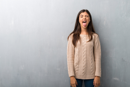 Teenager girl with sweater on a vintage wall showing tongue at the camera having funny look