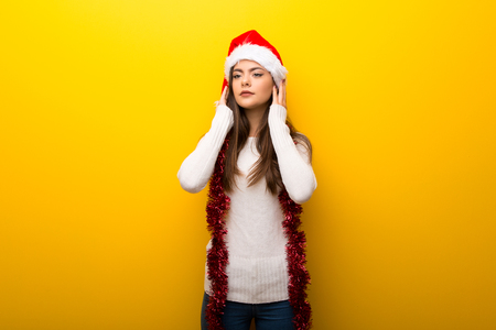 Teenager girl celebrating christmas holidays covering both ears with hands