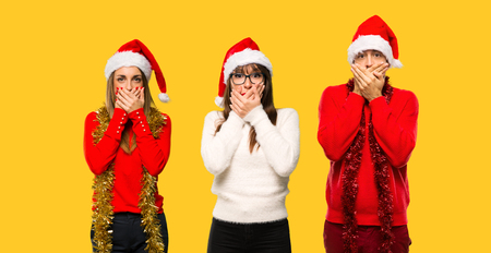 A group of people Blonde woman dressed up for christmas holidays covering mouth for saying something inappropriate. Can not speak on yellow background