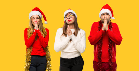 A group of people Blonde woman dressed up for christmas holidays keeps palm together. Person asks for something on yellow background Zdjęcie Seryjne