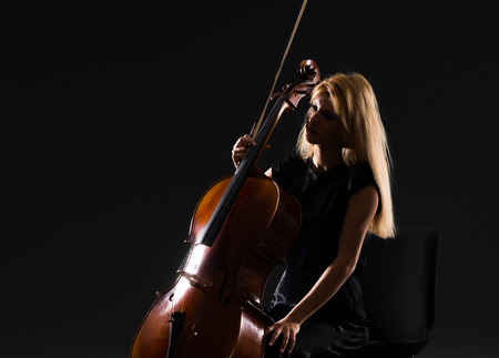Young girl playing the cello on isolated black background Stok Fotoğraf