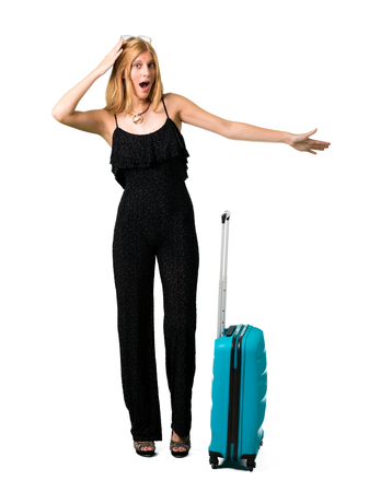 Blond girl traveling with her suitcase with surprise and shocked facial expression. Gaping because can not believe what is happening on isolated white background