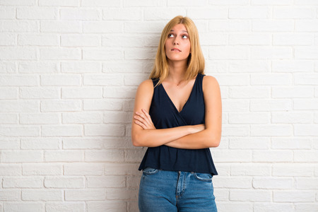 Blonde woman having doubts and with confuse face expression while bites lip. Questioning an idea on white brick wall background Stock Photo