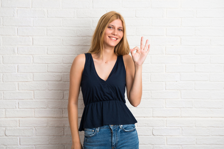 Blonde woman makes funny and crazy face emotion on white brick wall background