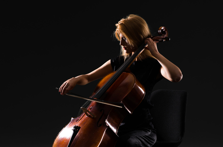 Young girl playing the cello on isolated black background 写真素材