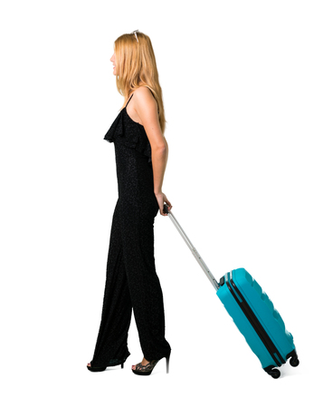 blond girl traveling with her suitcase walking on isolated white background