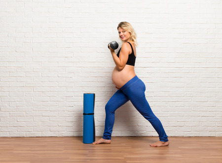 Sport blonde pregnant woman doing exercise indoors making weightlifting