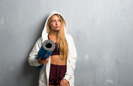 Young sport woman with mat Imagens