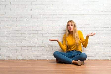 Young girl sitting on the floor having doubts and with confuse face expression