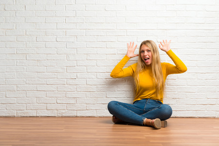 Young girl sitting on the floor with surprise and shocked facial expression Foto de archivo