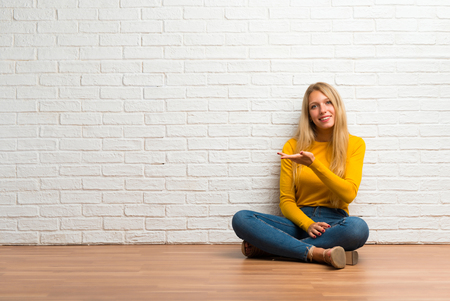 Young girl sitting on the floor presenting an idea while looking smiling towards