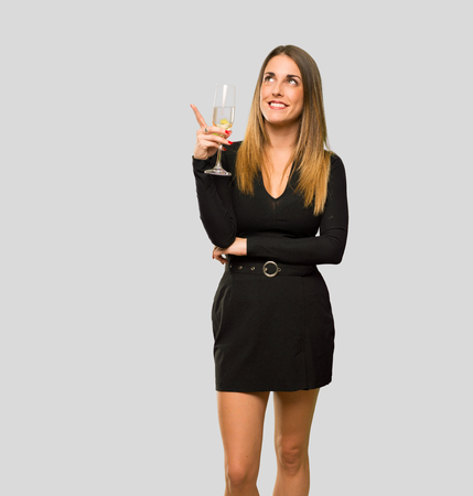 Woman with champagne celebrating new year 2019 pointing with the finger a great idea and looking up on isolated grey background