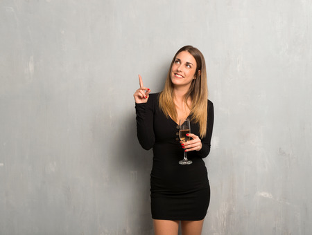Woman with champagne celebrating new year 2019 pointing with the index finger a great idea