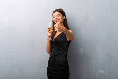 Teenager girl with champagne celebrating new year 2019 giving a thumbs up gesture and smiling