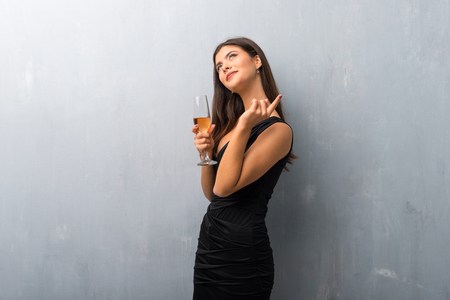 Teenager girl with champagne celebrating new year 2019 pointing with the index finger a great idea