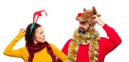 Couple dressed up for the christmas holidays having doubts and with confuse face while scratching head on isolated background