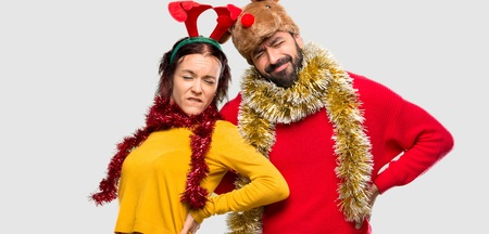 Couple dressed up for the christmas holidays suffering from backache for having made an effort on isolated background
