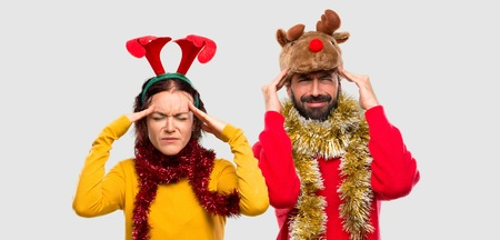 Couple dressed up for the christmas holidays unhappy with something. Negative facial expression on isolated background