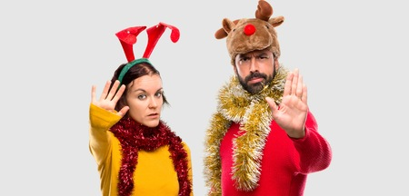 Couple dressed up for the christmas holidays making stop gesture with her hand denying a situation that thinks wrong on isolated background