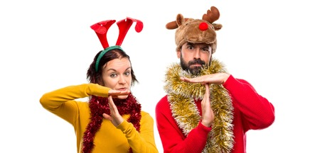 Couple dressed up for the christmas holidays making stop gesture with her hand to stop an act on isolated background