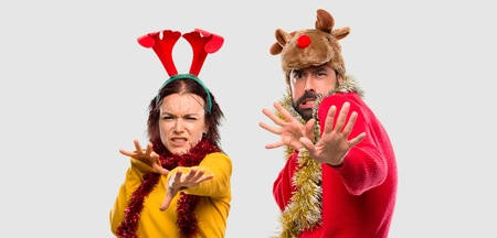 Couple dressed up for the christmas holidays is a little bit nervous and scared stretching hands to the front on isolated background