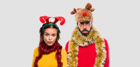 Couple dressed up for the christmas holidays with sad and depressed expression. Serious gesture on isolated background Stock Photo