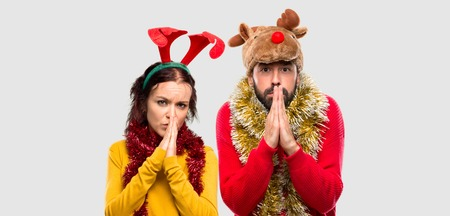 Couple dressed up for the christmas holidays keeps palm together. Person asks for something on isolated background