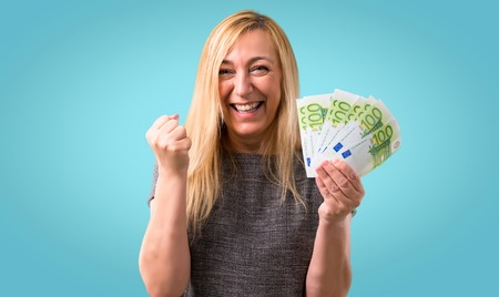 Middle-age blonde woman happy because has won a lot of money on colorful background Banco de Imagens