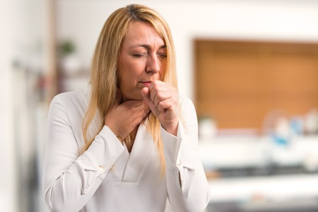 Middle age blonde woman with white shirt is suffering with cough and feeling bad at home Stock Photo