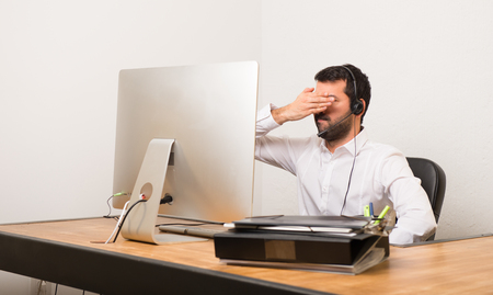 Telemarketer man in a office covering eyes by hands. Do not want to see something 版權商用圖片